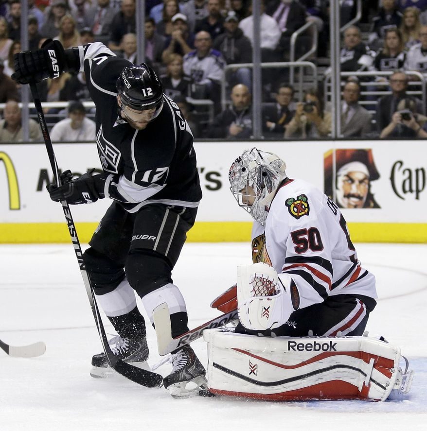 Chicago Blackhawks goalie Corey Crawford, right, blocks a shot by Los Angeles Kings right wing Marian Gaborik during the second period of Game 6 of the Western Conference finals of the NHL hockey Stanley Cup playoffs in Los Angeles, Friday, May 30, 2014. (AP Photo/Chris Carlson)