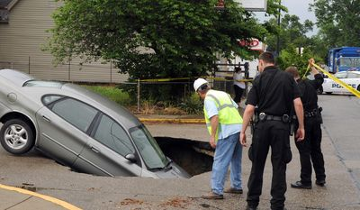 Evansville Policemen along with Chris Walsh, leftm look at a car that fell into a sink hole after a water main broke on Oregon St. at Main St. in Evansville, Ind. on Friday, May 30, 2014. The car's owner said he, his girlfriend and two children were in the car at the time. All got out safely from a passenger side door. (AP Photo/The Evansville Courier & Press, Kevin Swank)