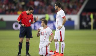 Switzerland's Xherdan Shaqiri, center, and Switzerland's Blerim Dzemaili, right, talk to the referee Neil Doyle of Ireland during the international friendly soccer match between Switzerland and Jamaica at the Swissporarena in Lucerne, Switzerland, Friday, May 30, 2014. Switzerland are preparing for the upcoming FIFA soccer World Cup in Brazil starting on 12 June. (AP Photo/Keystone, Peter Klaunzer)