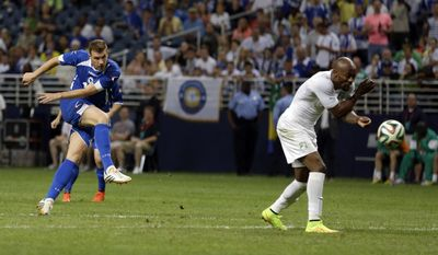 Bosnia-Herzegovina's Edin Dzeko, left, scores past Ivory Coast's Didier Zokora during the second half in an international friendly soccer match Friday, May 30, 2014, in St. Louis. Dzeko scored both goals in the team's 2-1 victory. (AP Photo/Jeff Roberson)