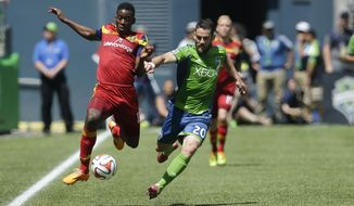 Seattle Sounders' Zach Scott (20) and  Real Salt Lake's Olmes Garcia, left, get airborne as they chase down a ball along the sideline in the first half of an MLS soccer match, Saturday, May 31, 2014, in Seattle. (AP Photo/Ted S. Warren)