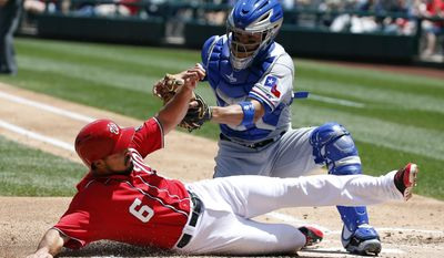 Washington Nationals' Anthony Rendon slides under the tag of Texas Rangers catcher Robinson Chirinos during the second inning of a baseball game at Nationals Park Saturday, May 31, 2014, in Washington. (AP Photo/Alex Brandon)