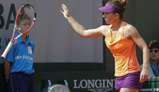 Romania's Simona Halep throws her racket away after missing a return during the third round match of the French Open tennis tournament against Spain's Maria-Teresa Torro-Flor at the Roland Garros stadium, in Paris, France, Saturday, May 31, 2014. (AP Photo/Michel Euler)