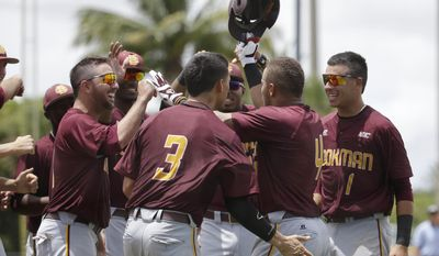 Bethune-Cookman's Josh Johnson, second from right, is congratulated by his teammates after hitting a solo home run in the first inning against Columbia of an NCAA college baseball regional tournament in Coral Gables, Fla., Saturday, May 31, 2014. (AP Photo/Lynne Sladky)