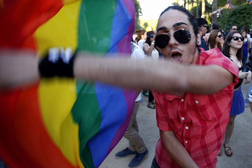 ** FILE ** A man with a flag dances during a first gay pride parade in downtown Nicosia, Cyprus, Saturday, May 31, 2014. Several thousand people have turned out for Cyprus' first gay pride parade, an event which organizers say show that Cypriots are shedding their conservative views. (AP Photo/Petros Karadjias)