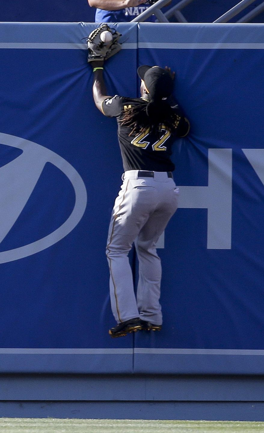Pittsburgh Pirates center fielder Andrew McCutchen can't a glove on a ball that went for a two-run triple by Los Angeles Dodgers' Drew Butera during fourth inning of a baseball in Los Angeles, Saturday, May 31, 2014. (AP Photo/Chris Carlson)
