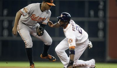 Houston Astros' Dexter Fowler (21) advances to second past Baltimore Orioles second baseman Jonathan Schoop after a wild pitch by Chris Tillman during the third inning of a baseball game, Saturday, May 31, 2014, in Houston. (AP Photo/Patric Schneider)