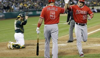 Los Angeles Angels' Mike Trout, right, celebrates his solo home run with teammate Albert Pujols (5) during the fourth inning of a baseball game Friday, May 30, 2014, in Oakland, Calif. (AP Photo/Marcio Jose Sanchez)