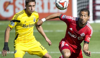Toronto FC defender Justin Morrow, right, eyes the ball next to Columbus Crew midfielder Ethan Finlay during the first half of an MLS soccer game in Toronto on Saturday, May 31, 2014. (AP Photo/The Canadian Press, Nathan Denette)