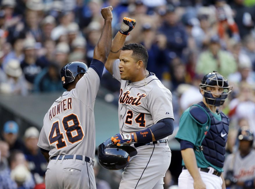 Detroit Tigers' Miguel Cabrera (24) is congratulated by teammate Torii Hunter after hitting a two-run home run as Seattle Mariners catcher Mike Zunino looks on in the third inning of a baseball game on Friday, May 30, 2014, in Seattle. (AP Photo/Elaine Thompson)