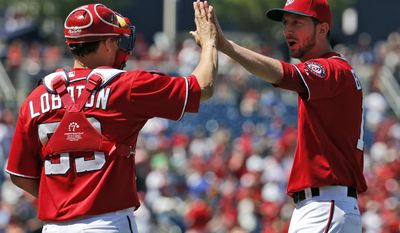 Washington Nationals catcher Jose Lobaton, left, celebrates with relief pitcher Jerry Blevins after their 10-2 win in a baseball game against the Texas Rangers at Nationals Park Saturday, May 31, 2014, in Washington. (AP Photo/Alex Brandon)