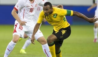 Xherdan Shaqiri of Switzerland, left, and Rodolph Austin of Jamaika fight for the ball, during the international friendly soccer match between Switzerland and Jamaica at the swissporarena in Lucerne, Switzerland, Friday, May 30, 2014. Switzerland are preparing for the upcoming FIFA soccer World Cup in Brazil starting on 12 June. (AP Photo/Keystone, Sigi Tischler)