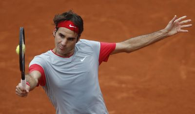 Switzerland's Roger Federer returns the ball to Russia's Dmitry Tursunov during the third round match of  the French Open tennis tournament at the Roland Garros stadium, in Paris, France, Friday, May 30, 2014. (AP Photo/Darko Vojinovic)