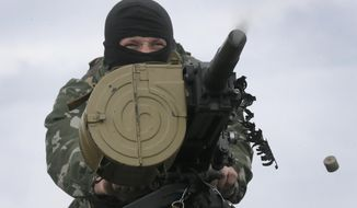 A Ukrainian soldier shoots from a grenade launcher, AGS-17 during a battle with pro-Russian separatist fighters at Slovyansk, Ukraine, Saturday, May 31, 2014. The Ukrainian Acting Defence Minister said on Friday that troops had ousted separatists from southern and western parts of the Donetsk region and north of the Luhansk region. (AP Photo/Efrem Lukatsky)