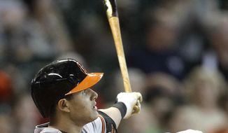 Baltimore Orioles' Manny Machado hits a grand slam to left field scoring Jonathan Schoop, David Lough, and Nick Markakis during the sixth inning of a baseball game against the Houston Astros, Sunday, June 1, 2014, in Houston. (AP Photo/Patric Schneider)