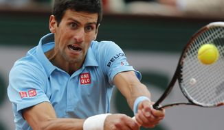 Serbia's Novak Djokovic returns the ball to France's Jo-Wilfried Tsonga during their fourth round match of  the French Open tennis tournament at the Roland Garros stadium, in Paris, France, Sunday, June 1, 2014. (AP Photo/David Vincent)