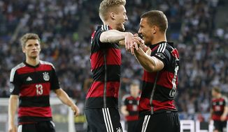 Germany's Thomas Mueller\, from left, Germany's Andre Schuerrle\ and Germany's Lukas Podoslki celebrate scoring during a friendly WCup preparation soccer match between Germany and Cameroon in Moenchengladbach, Germany, Monday, June 2, 2014. (AP Photo/Frank Augstein)