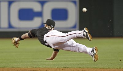 Arizona Diamondbacks second baseman Aaron Hill can't catch an RBI single by Cincinnati Reds' Todd Frazier during the fourth inning of a baseball game, Saturday, May 31, 2014, in Phoenix. (AP Photo/Ralph Freso)