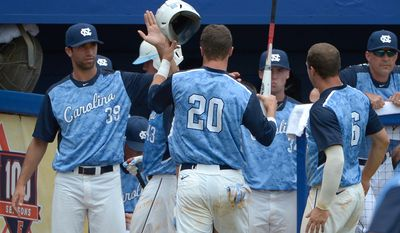 North Carolina's Skye Bolt (20) is congratulated by teammates Benton Moss (39), Colby Barnette (34) and Alex Raburn (6) after scoring on a single by Tyler Ramirez during the third inning of an NCAA college baseball regional tournament game against Long Beach State in Gainesville, Fla., Sunday, June 1, 2014. (AP Photo/Phelan M. Ebenhack)