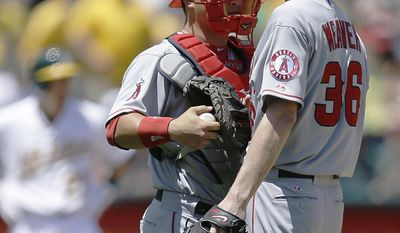 Los Angeles Angels' Jered Weaver, right, speaks with catcher Hank Conger in the third inning of a baseball game Sunday, June 1, 2014, in Oakland, Calif. (AP Photo/Ben Margot)