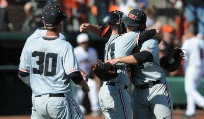 Oregon State catcher Logan Ice (33) hugs pitcher Ben Wetzler while teammage Michael Howard (30) joins in the Beavers celebration of defeating UNLV 6-1 in an NCAA college baseball regional tournament game in Corvallis, Ore., Sunday, June 1, 2014. (AP Photo/Mark Ylen)