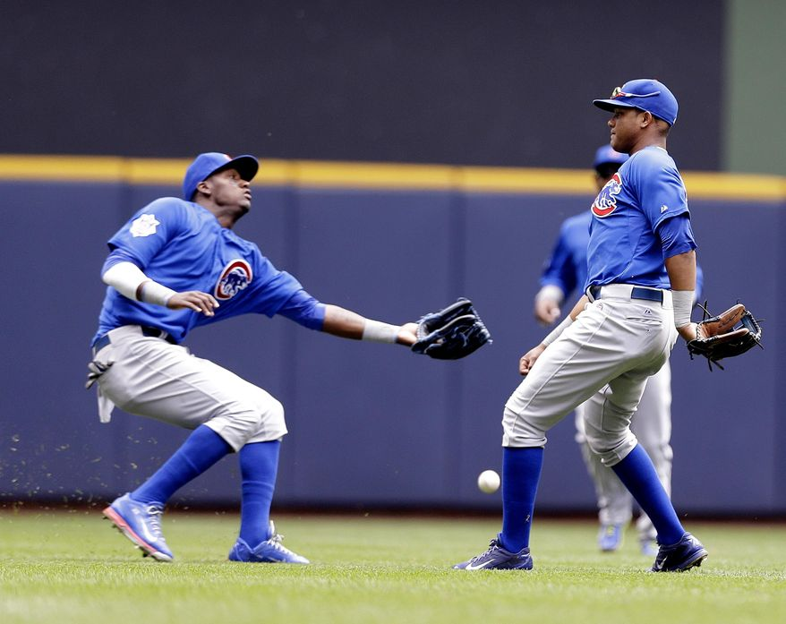 Chicago Cubs' Junior Lake, left, and Starlin Castro cannot come up with a double hit by Milwaukee Brewers' Scooter Gennett in the second inning of a baseball game on Sunday, June 1, 2014, in Milwaukee. (AP Photo/Jeffrey Phelps)