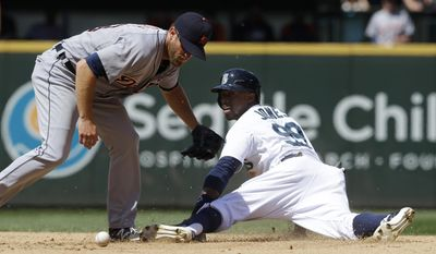Seattle Mariners' James Jones gets by Detroit Tigers second baseman Danny Worth, left, in the fifth inning of a baseball game, Sunday, June 1, 2014, in Seattle. (AP Photo/Ted S. Warren)