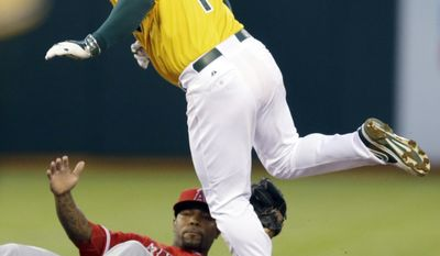 Oakland Athletics' Nick Punto (1) hops over Los Angeles Angels' Howie Kendrick after Punto was tagged out on a stolen base attempt in the third inning of a baseball game Saturday, May 31, 2014, in Oakland, Calif. (AP Photo/Ben Margot)