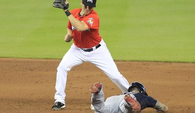 Atlanta Braves' Jordan Schafer, bottom, slides safely into second base with a steal in the ninth inning as Miami Marlins second baseman Ed Lucas tries to make the tag during a baseball game in Miami, Sunday, June 1, 2014. (AP Photo/Joe Skipper)