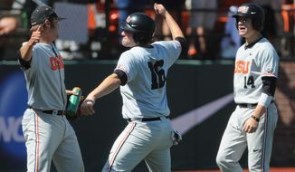 Oregon State starting pitcher Ben Wetzler, left celebrates runs scored by Beavers' Gabe Clark (16) and Caleb Hamilton (14) againt UNLV during an NCAA college baseball regional tournament game in Corvallis, Ore., Sunday, June 1, 2014. (AP Photo/Mark Ylen)