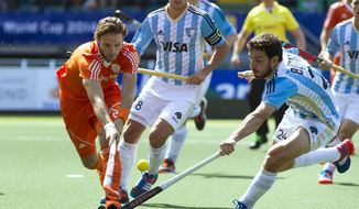 Netherlands' Rogier Hofman, left, battles for the ball with Argentina's Manuel Bruneta during their Field Hockey World Cup match in The Hague, Netherlands, Sunday June 1, 2014.  (AP Photo/Patrick Post)