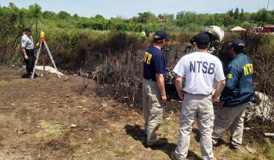 In this Sunday, June 1, 2014, photo provided by the National Transportation Safety Board, shows NTSB investigators at the scene of a plane that plunged down an embankment and erupted in flames during a takeoff attempt Saturday night at Hanscom Field in Bedford, Mass. The co-owner of the Philadelphia Inquirer newspaper, Lewis Katz, was killed along with six other people in the crash just days after reaching a deal that many hoped would end months of infighting at the newspaper and help restore it to its former glory. (AP Photo/National Transportation Safety Board)
