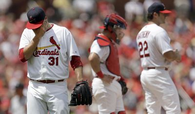 St. Louis Cardinals starting pitcher Lance Lynn, left, walks off the field after being pulled by manager Mike Matheny, right, as catcher Tony Cruz stands by during the fourth inning of a baseball game against the San Francisco Giants, Sunday, June 1, 2014, in St. Louis. (AP Photo/Jeff Roberson)
