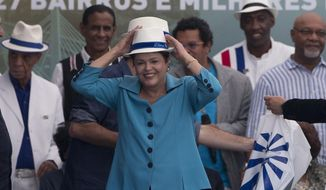 Brazil's President Dilma Rousseff, center, puts a hat during the inauguration of the BRT Transcarioca (Rapid Transit Bus) in Rio de Janeiro, Brazil, Sunday, June 1, 2014. The corridor has 39 kilometers long, cutting through 27 neighborhoods and will serve 320 thousand people every day, reducing in 60 per cent the average time of the commute. The corridor will connect the International Airport to the subway, which takes the passengers to the Maracana stadium. (AP Photo/Silvia Izquierdo)