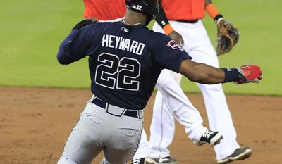 Atlanta Braves' Jason Heyward is forced out by Miami Marlins second baseman Derek Dietrich, left, as shortstop Adeiny Hechavarria looks on at right, on a fielder's choice which scored Atlanta Braves' Andrelton Simmons in the third inning during their baseball game in Miami, Sunday, June 1, 2014. (AP Photo/Joe Skipper)