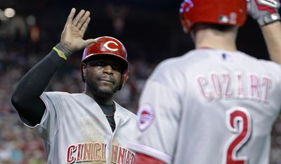 Cincinnati Reds' Brandon Phillips, left, is congratulated by Zack Cozart (2) after scoring a run against the Arizona Diamondbacks during the fourth inning of a baseball game, Saturday, May 31, 2014, in Phoenix. (AP Photo/Ralph Freso)