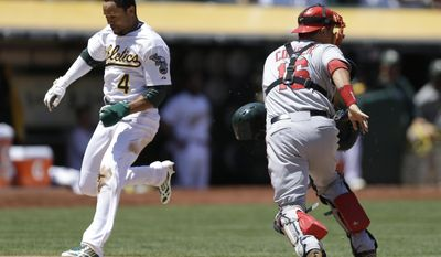 Oakland Athletics' Coco Crisp, left, scores past Los Angeles Angels catcher Hank Conger in the third inning of a baseball game Sunday, June 1, 2014, in Oakland, Calif. Crisp scored on a single by Josh Donaldson.(AP Photo/Ben Margot)