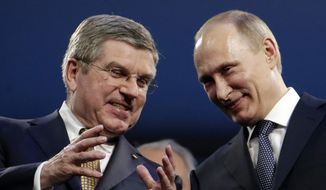International Olympic Committee President Thomas Bach, left, and Russian President Vladimir Putin watch the closing ceremony of the 2014 Winter Olympics, Sunday, Feb. 23, 2014, in Sochi, Russia. (AP Photo/Charlie Riedel)