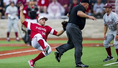 Indiana third baseman Dustin DeMuth (16) collides with third-base umpire Tony Maners while going after a passed ball during an NCAA college baseball regional tournament game against Stanford in Bloomington, Ind., Sunday, June 1, 2014. (AP Photo/Doug McSchooler)