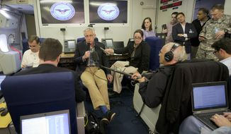 U.S. Defense Secretary Chuck Hagel, center, is seen aboard a U.S. Military Aircraft before speaking to members of the media during his flight, Sunday, June 1, 2014. Hagel spoke about the released of U.S. Army Sgt. Bowe Bergdahl who was held hostage in Afghanistan, and who was handed over Saturday morning by members of the Taliban in exchange for five Afghan detainees held at the military prison in Guantanamo Bay prison in Cuba. (AP Photo/Pablo Martinez Monsivais, Pool)
