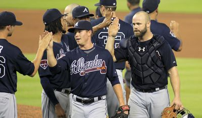 Atlanta Braves catcher Evan Gattis, right, and relief pitcher Shae Simmons, center, celebrate with teammates after defeating the Miami Marlins 4-2 in their baseball game in Miami, Sunday, June 1, 2014. (AP Photo/Joe Skipper)