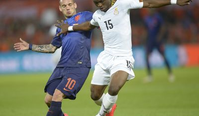 Netherlands' Wesley Sneijder left, fights for the ball with Rashid Sumaila from Ghana, during their international friendly soccer match between The Netherlands and Ghana at De Kuip stadium in Rotterdam, Netherlands, Saturday, May 31, 2014. (AP photo/Ermindo Armino)