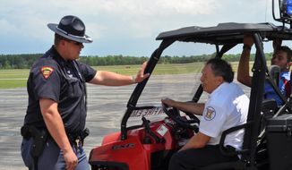 ** FILE ** A Wisconsin State Patrol trooper, left, speaks with Stockton Fire Department crew members following a plane crash at the Stevens Point Air Show, Sunday, June 1, 2014, in Stevens Point, Wis. Stevens Point police say the small plane crashed while performing aerial maneuvers at the airshow, killing the 47-year-old pilot. (AP Photo/Stevens Point Journal Media, B.C. Kowalski)