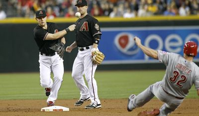 Arizona Diamondbacks shortstop Chris Owings, left, throws to first to complete a double play after forcing out Cincinnati Reds' Jay Bruce (32) as Diamondbacks' Aaron Hill looks on during the second inning of a baseball game on Saturday, May 31, 2014, in Phoenix. (AP Photo/Ralph Freso)