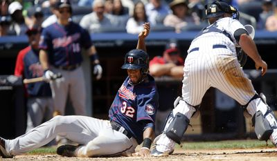Minnesota Twins' Aaron Hicks, left, scores past New York Yankees catcher Brian McCann, right, on a single by Minnesota Twins' Trevor Plouffe during the third inning of a baseball game on Sunday, June 1, 2014, in New York. (AP Photo/Jason DeCrow)