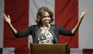 """First lady Michelle Obama asked the audience at a Democratic fundraiser in Boston to remember """"when we took office"""" but corrected herself and said, """"Well, when Barack took office and I was there.""""  (AP Photo/Stephan Savoia)"""