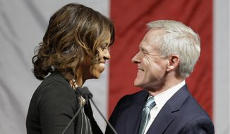 Navy Secretary Ray Mabus hugs first lady Michelle Obama as Mabus introduces her during a keel-laying ceremony for a submarine that will become the USS Illinois, Monday June 2, 2014, at the Electric Boat company in  North Kingstown, RI. (AP Photo/Stephan Savoia)