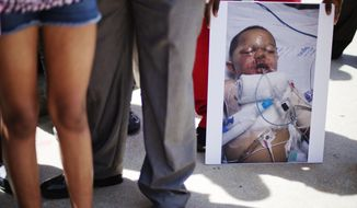 A photo of 19-month-old Bounkham Phonesavanh who was severely burned by a flash grenade during a SWAT drug raid, is held by a supporter during a vigil outside Grady Memorial Hospital where he is undergoing treatment, Monday, June 2, 2014, in Atlanta. A Georgia state senator says he will ask U.S. Attorney Sally Quillian Yates to investigate a police raid where the Georgia toddler was severely burned by a flash grenade. State Sen. Vincent Fort joined 19-month-old Bounkham Phonesavanh's family at a prayer vigil outside Grady Memorial Hospital in Atlanta on Monday. The boy's mother says a fever may delay a planned surgery. Police have said officers were looking for a suspect who may have been armed and didn't know children were inside. (AP Photo/David Goldman)