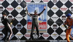 Helio Castroneves, center, celebrates his victory with Will Power, left, who finished second and Charlie Kimball, right, the third place finisher after the second race of the IndyCar Detroit Grand Prix auto racing doubleheader in Detroit Sunday, June 1, 2014.  (AP Photo/Bob Brodbeck)