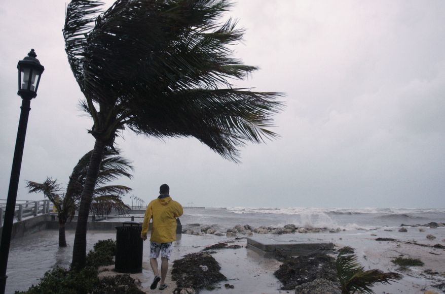 A man walks along the White Street pier as waves crash in Key West, Fla. Tuesday, Sept. 9,  2008. Hurricane Ike is passing to the south over Cuba. (AP Photo/Lynne Sladky)
